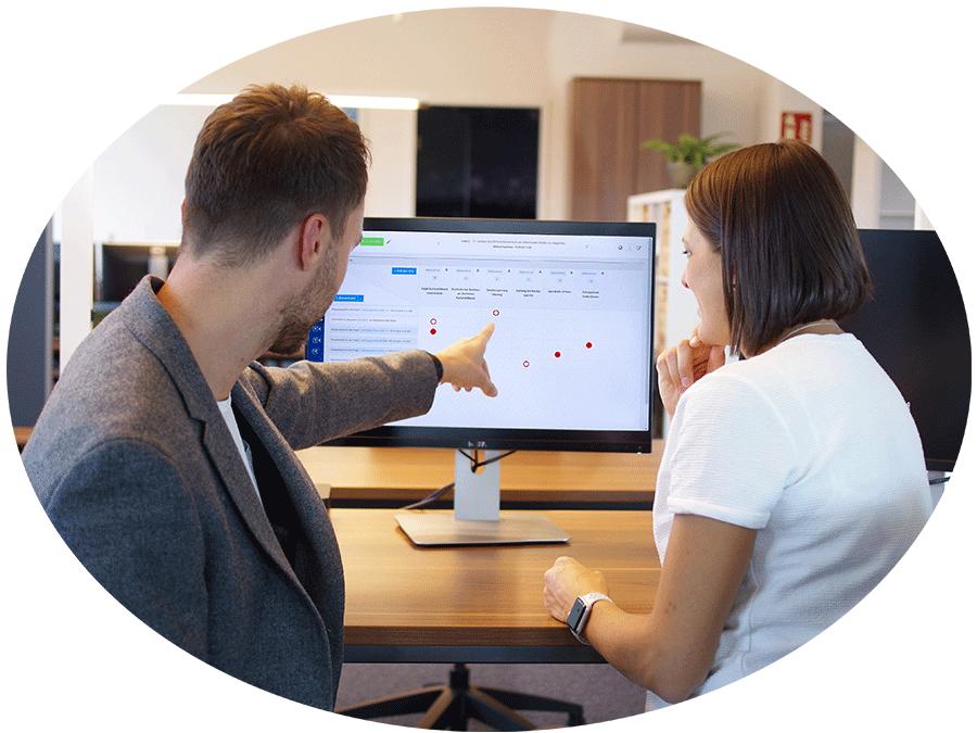 Eine Person zeigt einer anderen Person sitzend am Tisch etwas auf dem Bildschirm