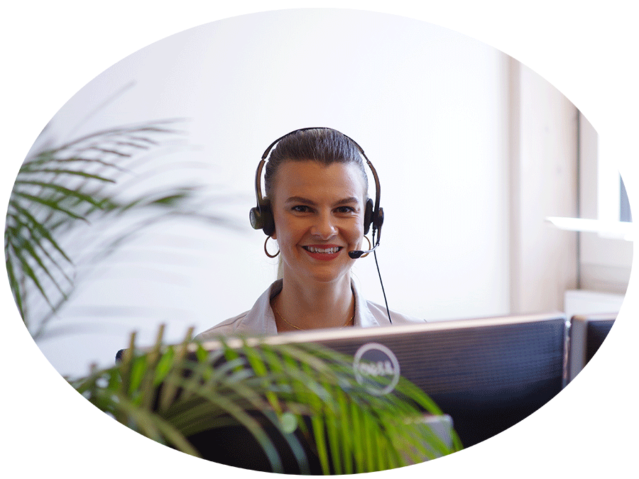 Eine Frau sitzt vor einem Bildschirm, hat ein Headset auf dem Kopf und schaut freundlich in die Kamera