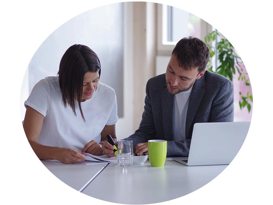 Zwei Personen arbeiten zusammen an einem Tisch und markieren stellen auf einem Blatt