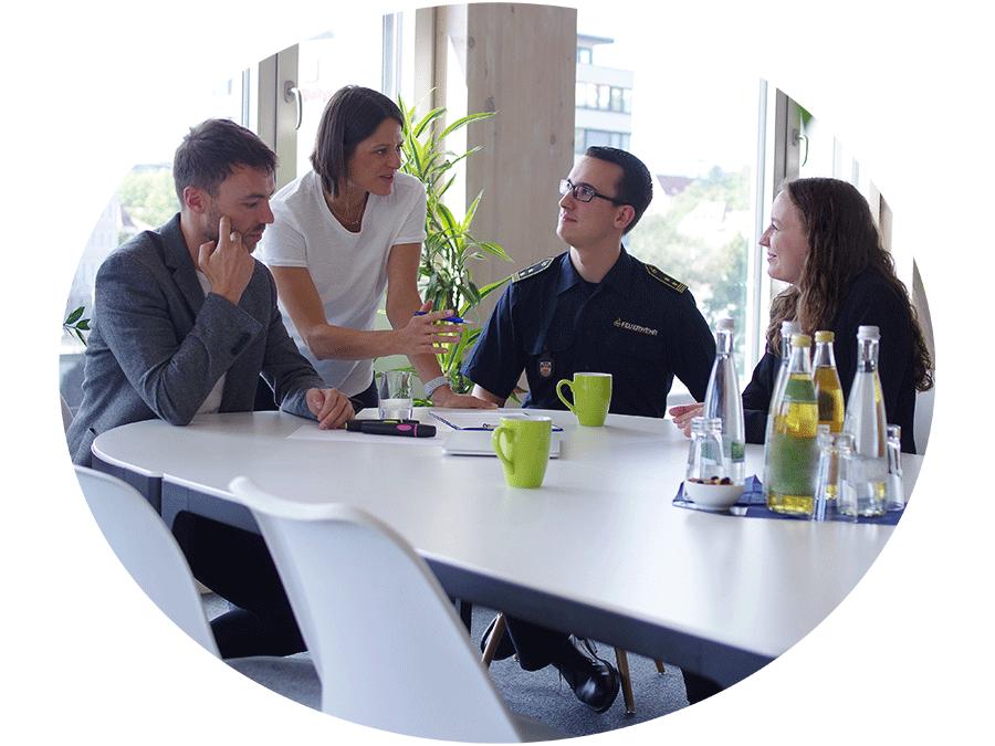 Vier Personen sitzen am Tisch und besprechen etwas