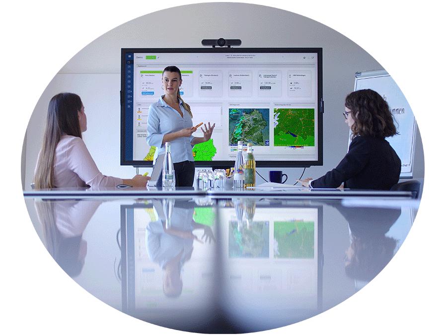 Eine stehende Person erklärt vor einem Smartboard zwei sitzenden Personen etwas